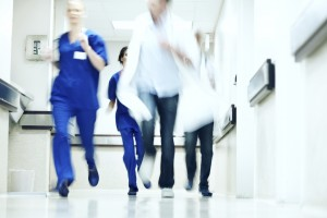 Blurred image of doctors running down a hospital corridor in an emergency